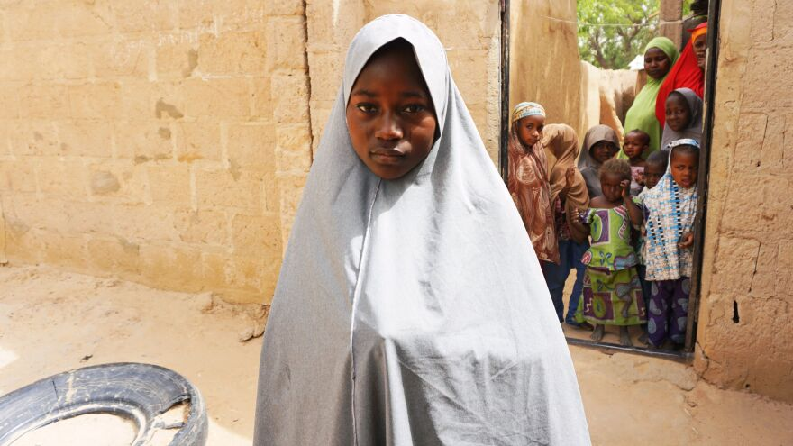 Hassana Mohammed, 13, who scaled a fence to escape Monday's alleged Boko Haram attack, stands outside her home in Dapchi, Nigeria, on Thursday.