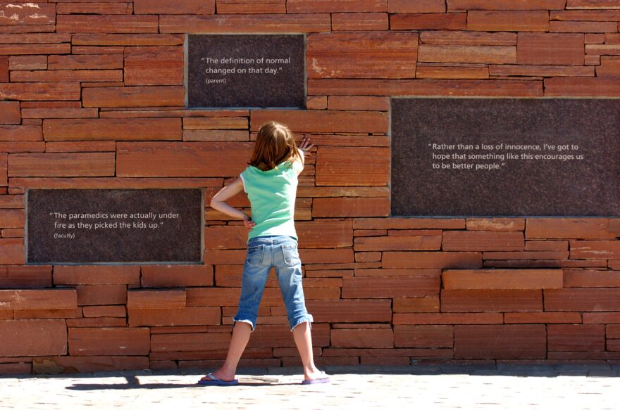 A young child reads the plaques at the Columbine Memorial near Rebel Hill and Columbine High School in Littleton, Colorado.