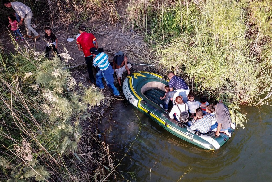 In this June 2019 file photo, a group of 11 migrants is guided by two smugglers crosses the Rio Grande in rafts near an area known as Rincon, in South McAllen, TX.