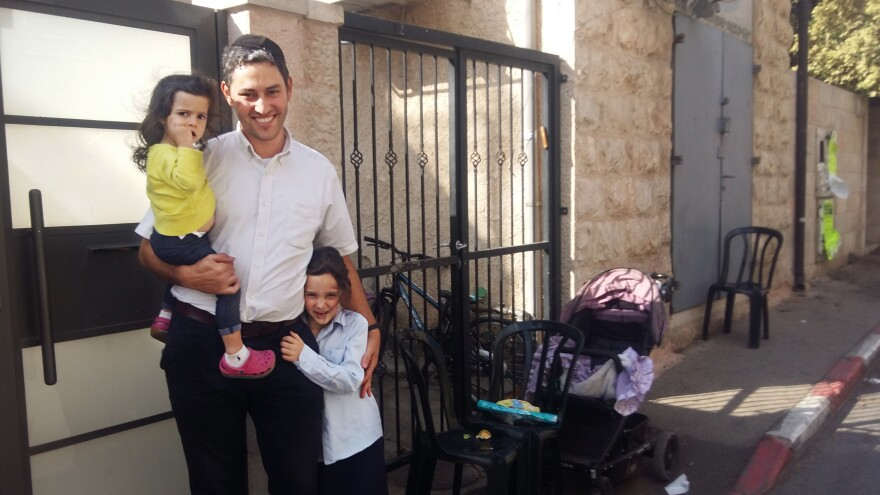 Yosef Eharman, 33, with his children, stands in front of their home in an ultra-Orthodox enclave of Jerusalem. Eharman recently left the Jewish seminary, or yeshiva, where he had studied since childhood, to train as an electrical engineer. He is now working in a solar energy company.