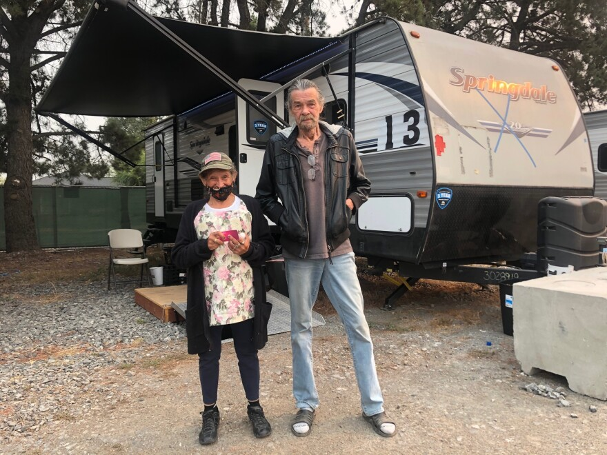 Carmen Almejo, 63, and Mitch Sinnett, 75, stand outside their trailer at the Sonoma County Fairgrounds. They were evacuated after the Glass Fire destroyed their transitional housing.