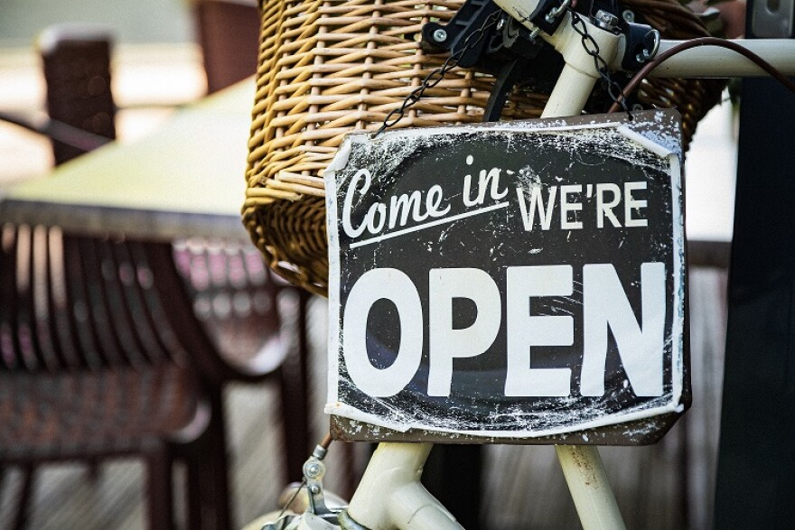 """A sign inside a shop says """"Come in, we're open."""""""