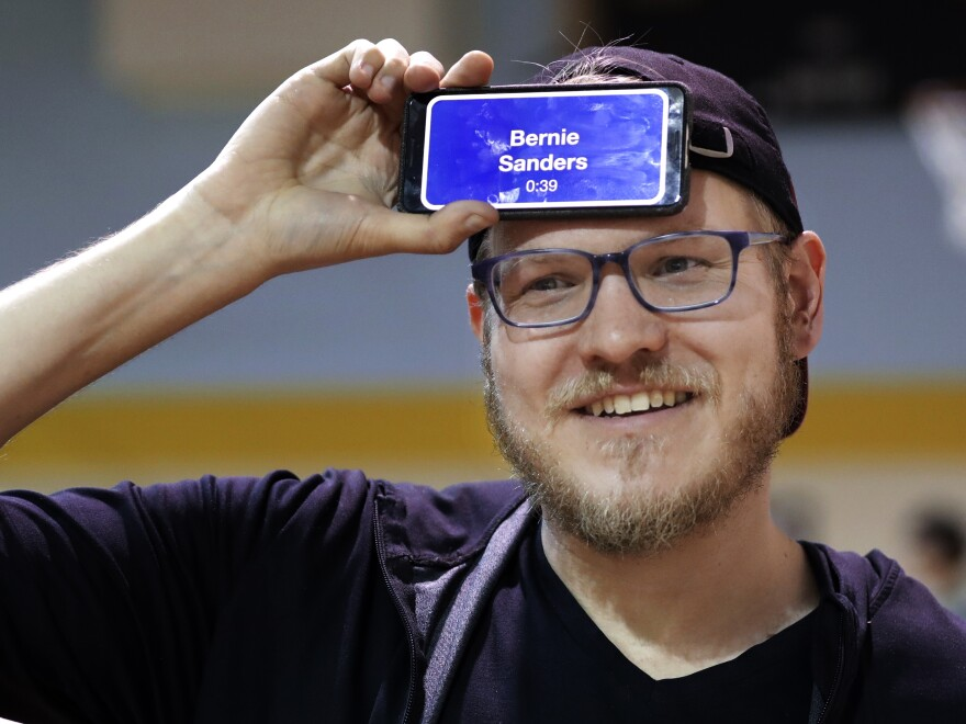 """Corey Brothers tries to guess the name of candidate Bernie Sanders as he plays the guessing game """"Heads Up!"""" while waiting in line to vote on Super Tuesday at the Cleveland Park Community Center precinct in Nashville, Tenn."""