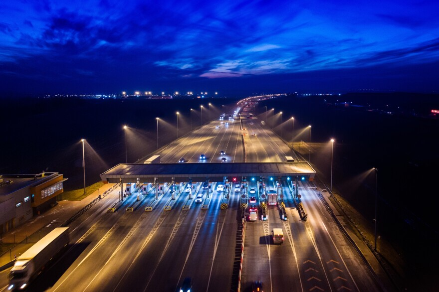 Aerial drone view on motorway with toll collection point at night