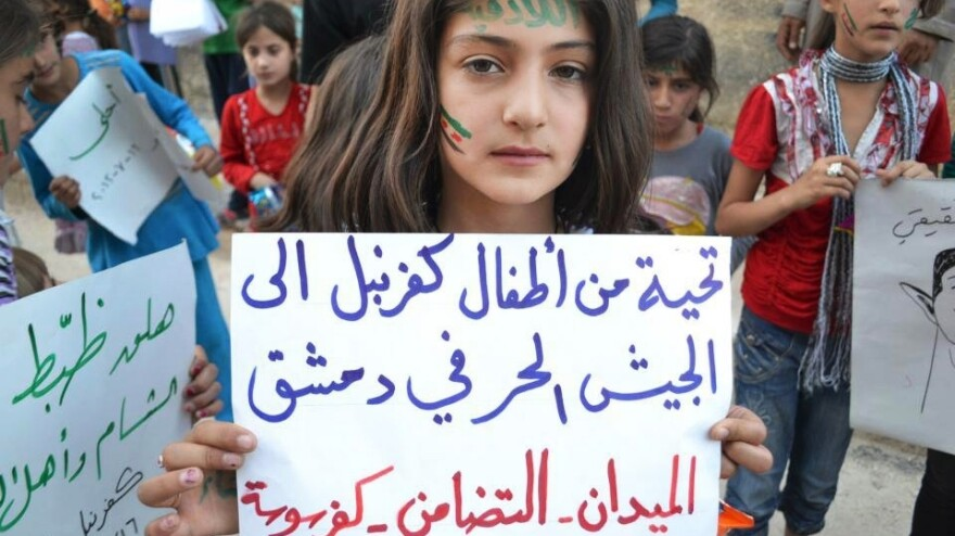 """In this image taken July 16, 2012, and provided by Edlib News Network, a Syrian girl holds a poster that reads, """"Greetings from Kfarnebel's children to the Free Syrian Army soldiers in Damascus,"""" during a demonstration in Kfarnebel, Syria. The image was part of an """"inside rebel-held Syria"""" series of stories by NPR's Kelly McEvers."""