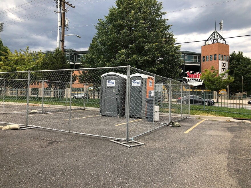 Photo of two grey portable bathrooms surrounded by a chain link fence in a parking lot. Smith's Ballpark is across the street in the background.