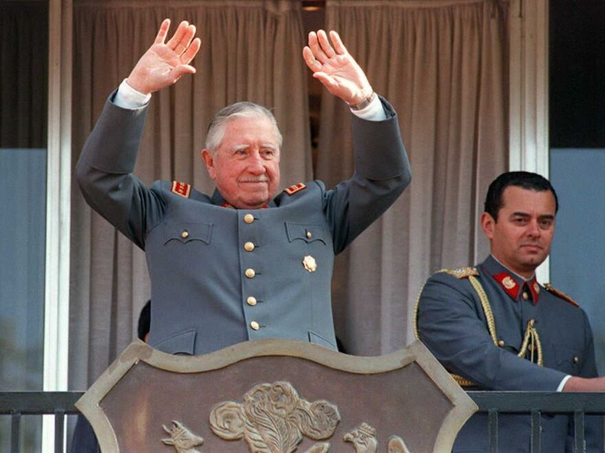 Gen. Augusto Pinochet waves to supporters from the balcony of his residence in Santiago, Chile, during the celebration of the 22nd anniversary of the 1973 military coup he led to oust President Salvador Allende.