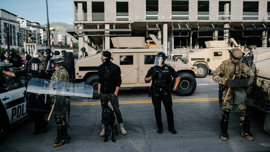 Photo of police officers and men in camouflage outfitted with riot gear. There are tan military vehicles and a police cruiser in the background.