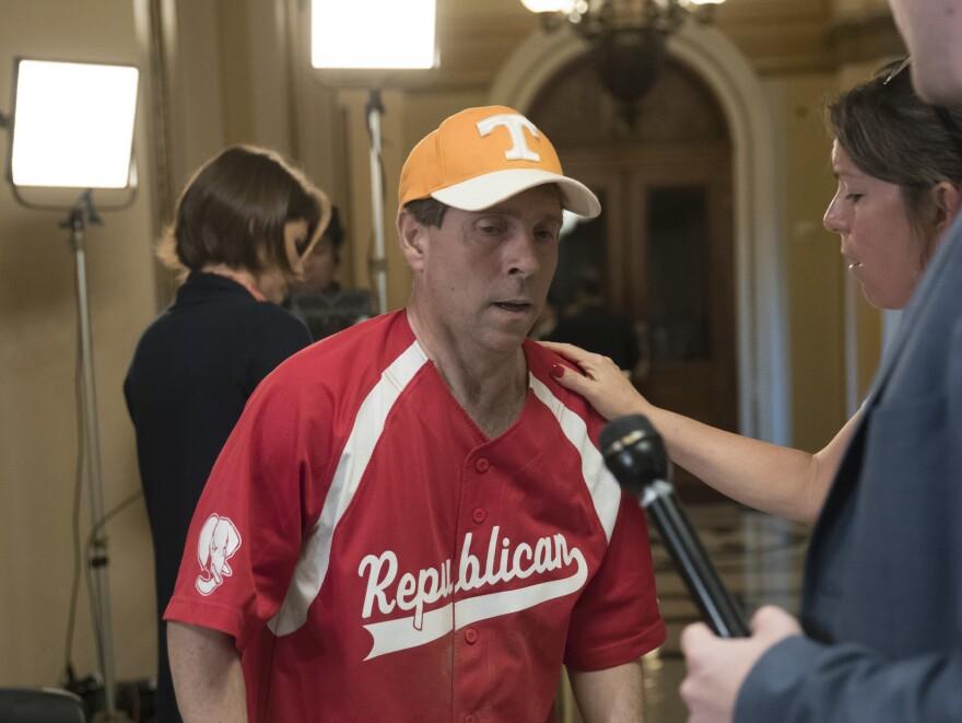Rep. Chuck Fleischmann, R-Tenn., still wearing his baseball uniform, describes to reporters on Capitol Hill the scene of a shooting at a congressional baseball practice.