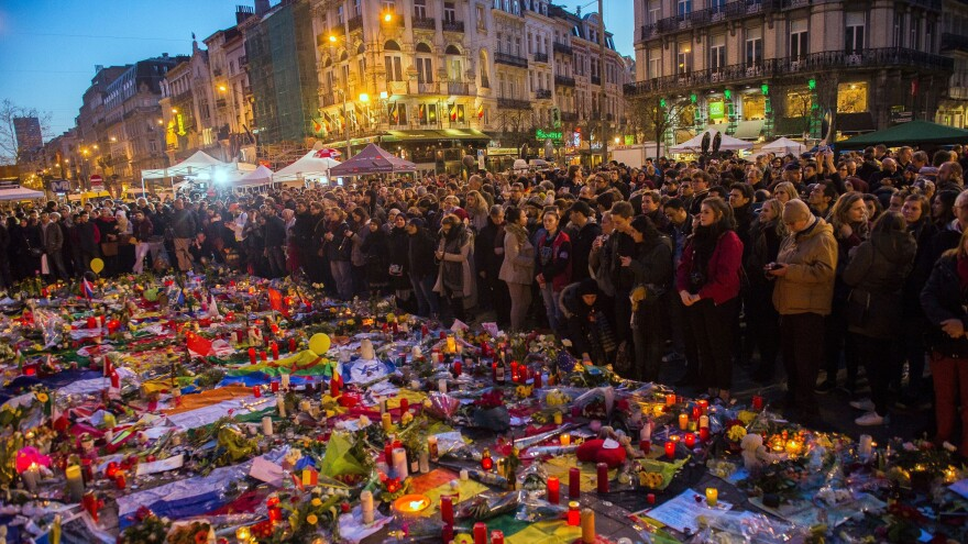 People gather Friday at a makeshift memorial in tribute to the victims of the Brussels terror attacks, on Place de la Bourse square in Brussels. Grieving Belgians held prayers in the rain for the victims, but there was also growing anger at the government for letting a string of militants slip through the net.