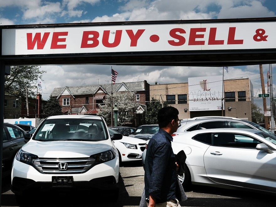 A man walks by a New York City auto dealership in 2017. Studies have found that African-Americans and Hispanics have systematically been charged a higher markup on auto loans than have white borrowers.