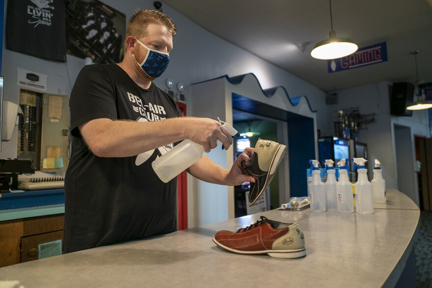 Dale Strom cleans a pair of bowling shoes at Bel-Air Bowl on June 26. The bowling alley reopened for the first time on Friday since the coronavirus closed businesses across the region. 06 26 2020