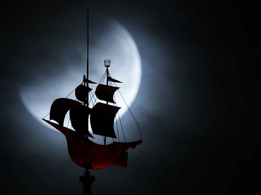 The Earth's shadow begins to fall on the moon as it goes behind a weather vane shaped like a Spanish galleon on the Freedom Tower in Miami.