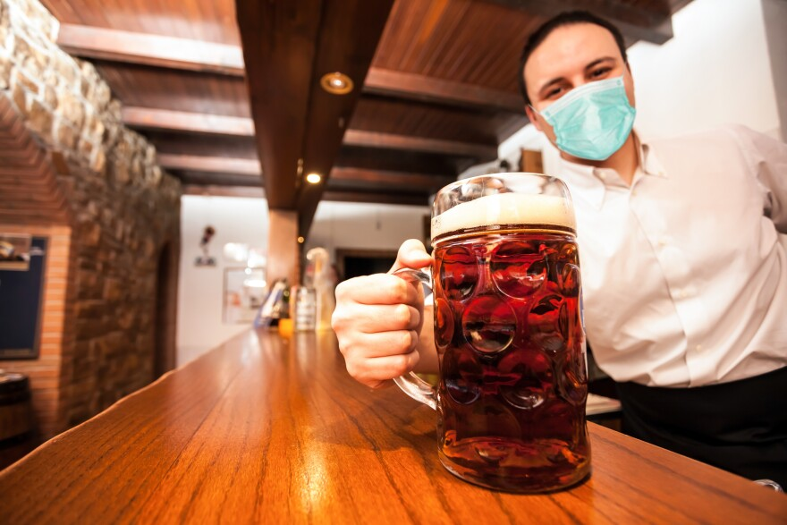 Masked bartender serving a giant beer during coronavirus pandemic