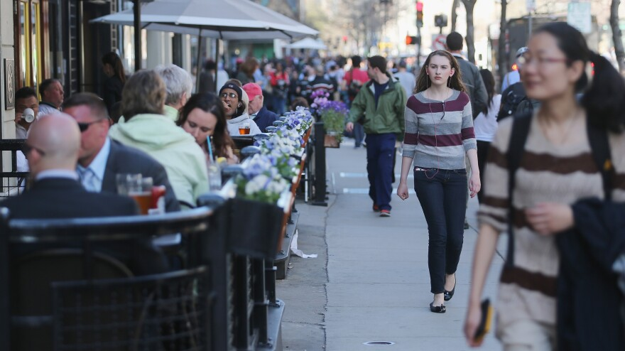 People walk and eat along Boylston Street, near the site of the Boston Marathon bombings, on Wednesday. Businesses in the area have reported strong customer support; they also have an option for federal loans to help them cope with losses.