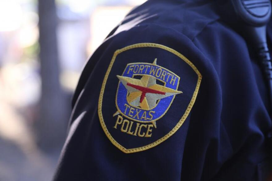"""The Fort Worth Police insignia patch on a police officer's shoulder. The insignia is a star with """"Fort Worth Texas Police"""" stitched behind it."""