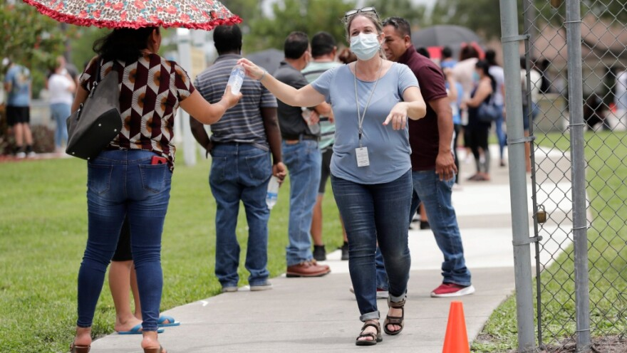 Woman in mask hands out bottles to people in line