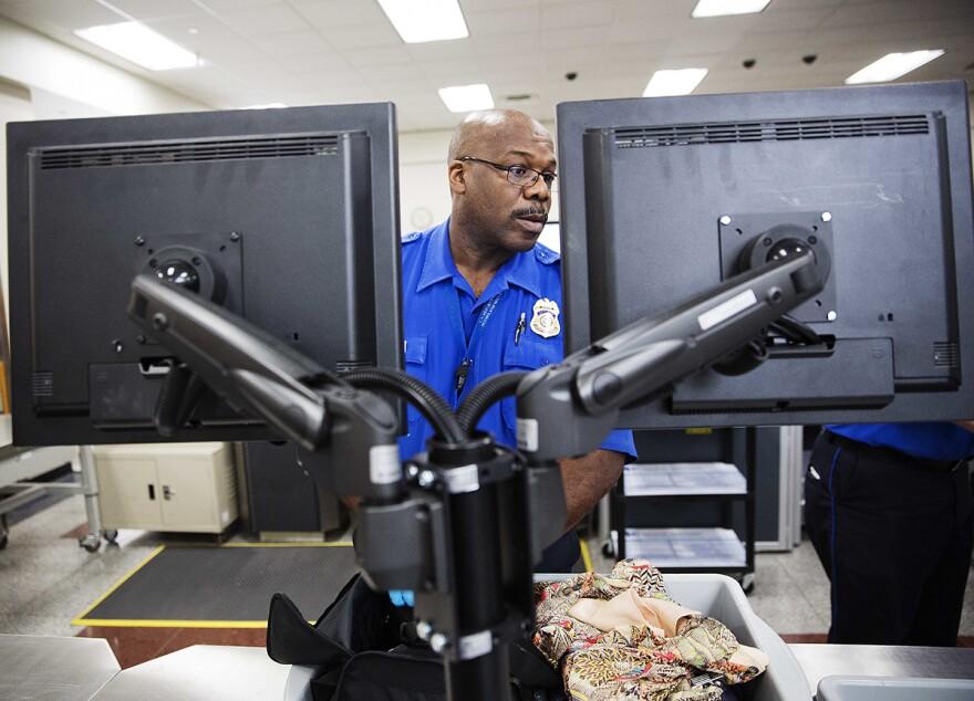 A TSA officer looks at a monitor while checking a bag in the screening lane at Hartsfield-Jackson Atlanta International Airport, May 25, 2016, in Atlanta. In 2017, TSA found more guns in carry-ons at the airport than at any other.