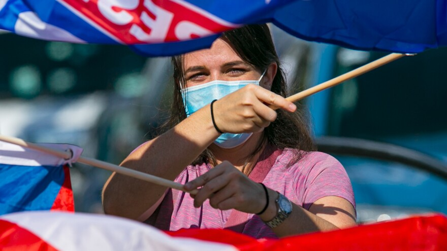 A person is waving flags during a political rally. The person is wearing a mask because of the coronavirus pandemic.