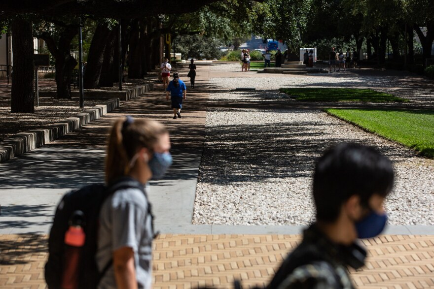 Students wearing face masks walk along UT campus earlier this month. Ahead of Halloween and other holidays, Austin's interim health authority is urging people to practice safety measures to avoid spreading the coronavirus.