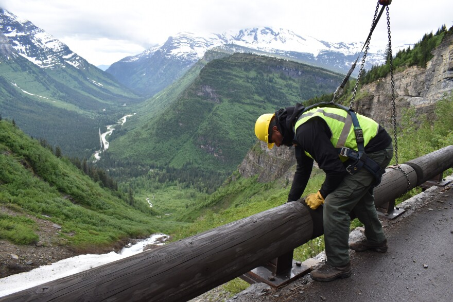 Road crew worker installs guard rail on the iconic Going to the Sun Road in Glacier National Park, MT.