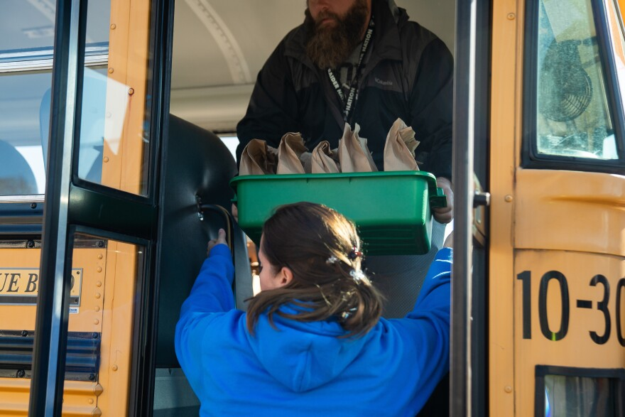 Nutrition staff, bus drivers, paraprofessionals and volunteers load prepared meals onto school busses on the first day of Franklin Pierce Schools' meal distribution program.