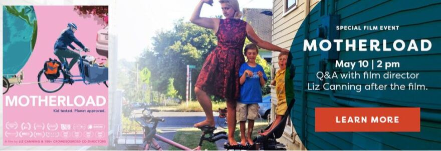 A woman wearing a red dress stands on a bike with two young boys. She's flexing her bicep.