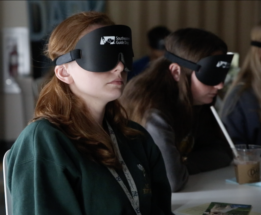 """Two women wearing blindfolds at """"Beyond the Dark"""" show."""