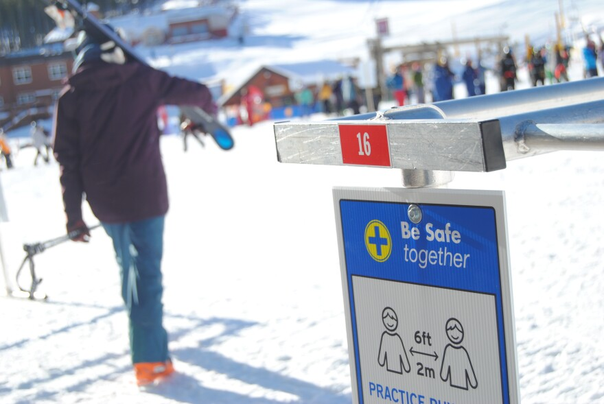 A skiier walks past a blue sign that says 'be safe together' and instructs people to stay six feet apart.