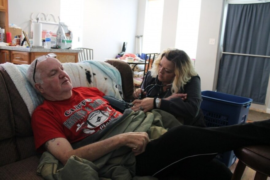 Kelly Browning checks Lyle Marcum's blood pressure during her weekly visit to his apartment in Matewan, West Virginia on May 14, 2019. Because Browning checks Marcum's vitals during every visit, she was able to respond immediately when she found his blood