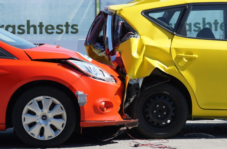 Collision between an orange sedan and a yellow hatchback