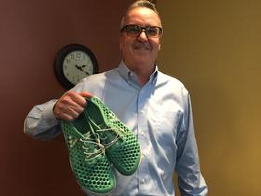 AECOM vice president Dan Levy holds a pair of shoes made entirely from biofoam derived from algae.