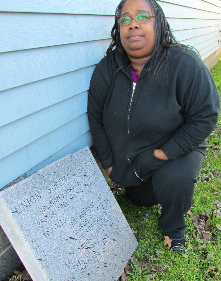 Debra Tarver, with the cornerstone from Union Baptist Church which she saved.