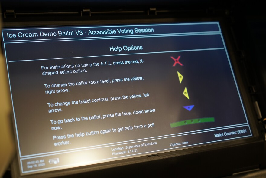 "A voting machine displays instructions detailing how to use an audio-tactile interface. It reads, ""For instructions on using the A.T.I. press the red, X-shaped select button. To change the ballot zoom level, press the yellow right arrow. To change the ballot contrast, press the yellow, left arrow. To go back to the ballot press the blue, down arrow now. Press the help button again to get help from a poll worker."""