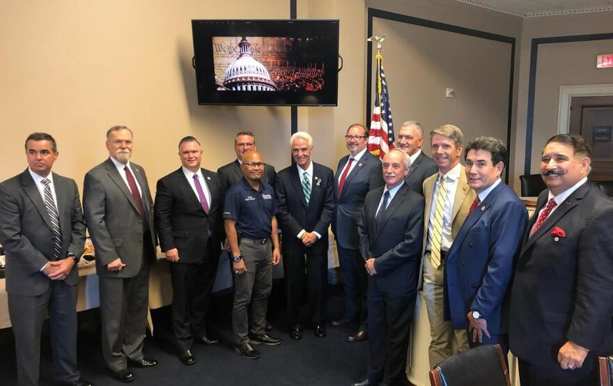 Charlie Crist and DJ Reyes stand with members of the National Veterans Court Alliance