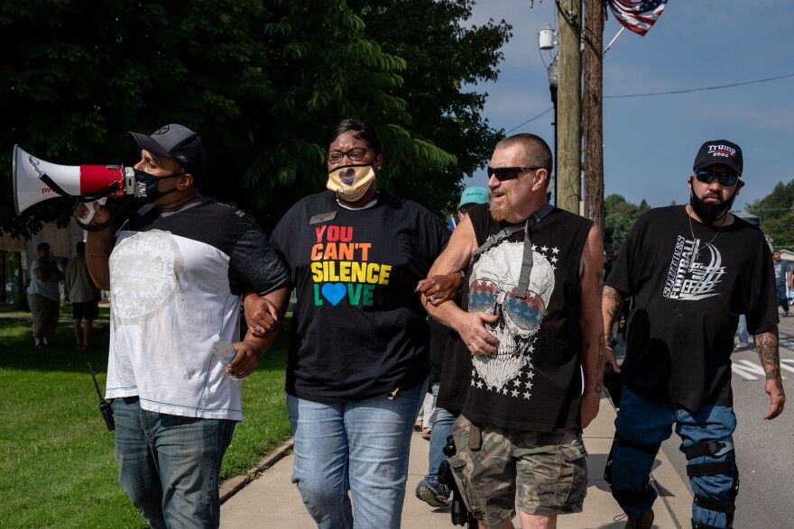 Danielle Walker arm in arm with counter protester