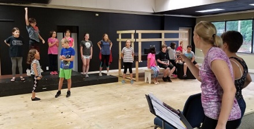 Artistic Director Cameron Garrett gives notes about choreography to summer camp students positioned around the stage at Making Light Productions.