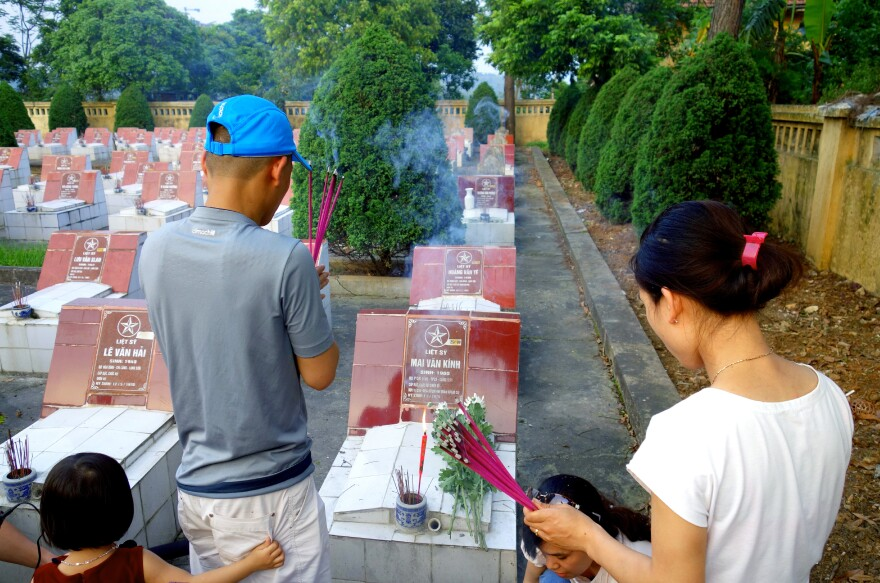 Pham Thi Ky (right) and her family pray at the grave of her brother-in-law, who was killed 36 years ago in the 1979 border war with China. Every year, the family goes to the cemetery on the anniversary of his death. Vietnam and China have been adversaries for centuries and the friction continues to this day.