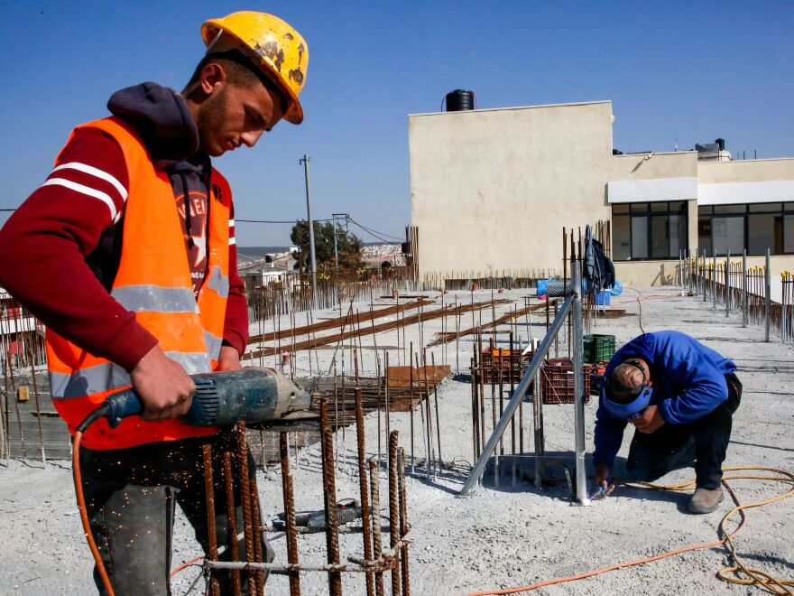 A construction worker saws steel rods at the site of a school that was funded by the United States Agency for International Development in the Palestinian village of al-Jabaa, in the West Bank, on Jan. 22.
