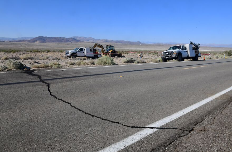 A crack on Highway 178 is seen as construction workers fix a broken water line south of Trona.