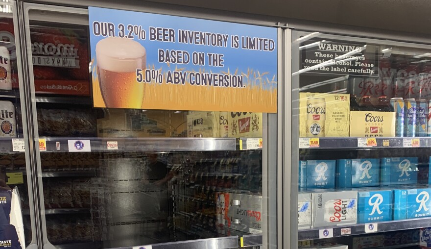 An empty beer cooler cooler with a sign that reads 'our 3.2% beer inventory is limited based on the 5% ABV conversion.
