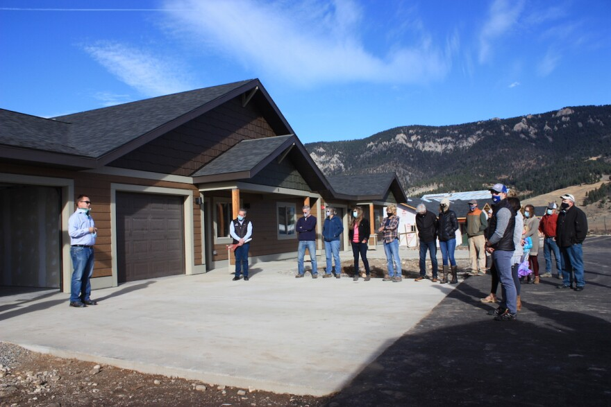 People gather around one of the first completed triplex units for teachers in Big Sky, Mont. during a ribbon cutting ceremony in Oct. 2020.