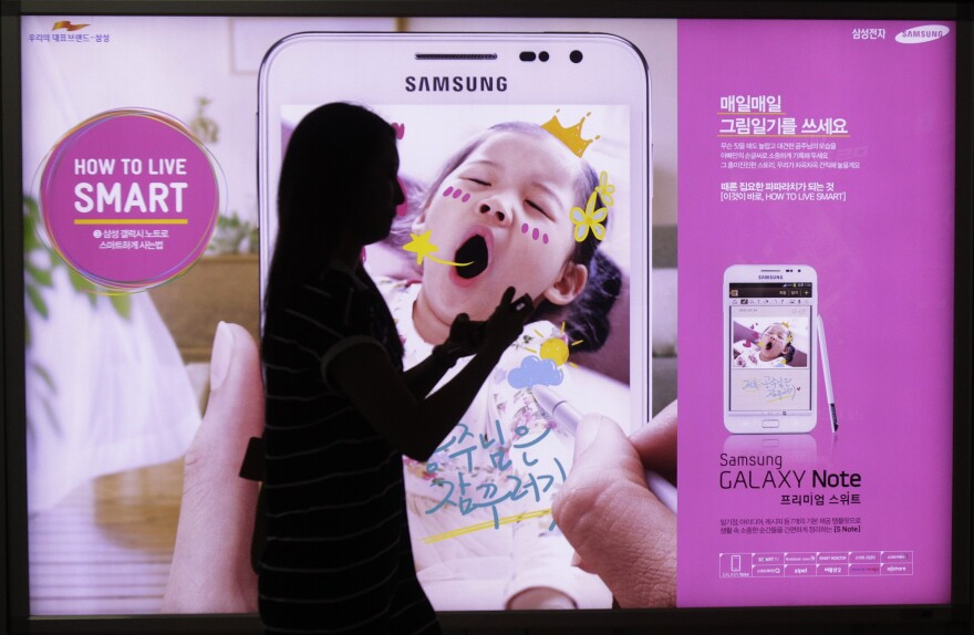 A woman walks across banner advertising for Samsung Electronics' Galaxy Note Seoul, South Korea on Monday.