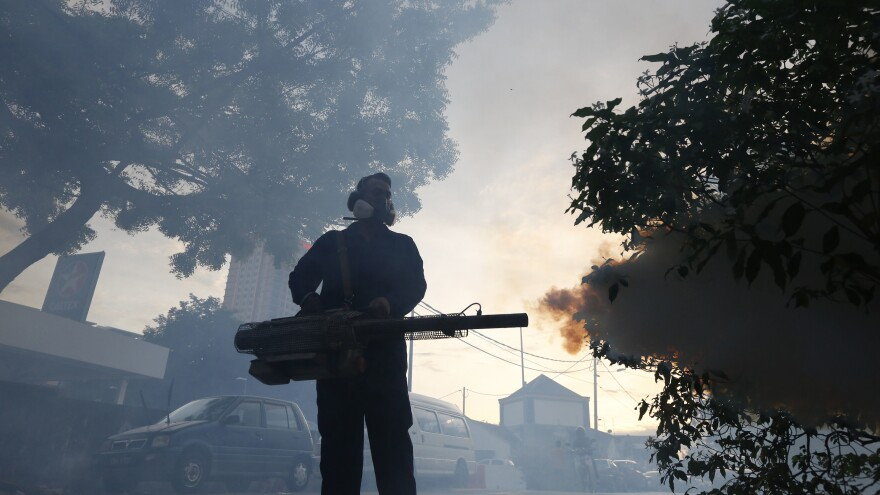 A government worker sprays mosquito insecticide fog in Kuala Lumpur, Malaysia, earlier this month to block the spread of Zika. The U.S. CDC advises pregnant women to reconsider plans to travel to Malaysia and 10 other countries because of the virus.