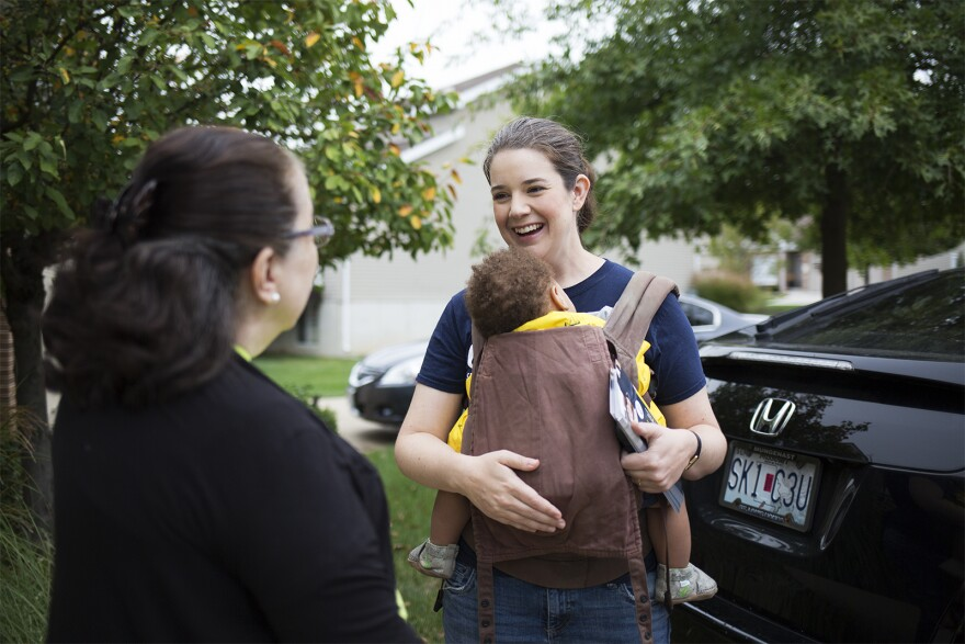 Mary Elizabeth Coleman holds her son Gerhardt while talking to voters and knocking doors in her district last month. Coleman, a lawyer and mother of six, has made her family a big part of her campaign. Oct. 2018