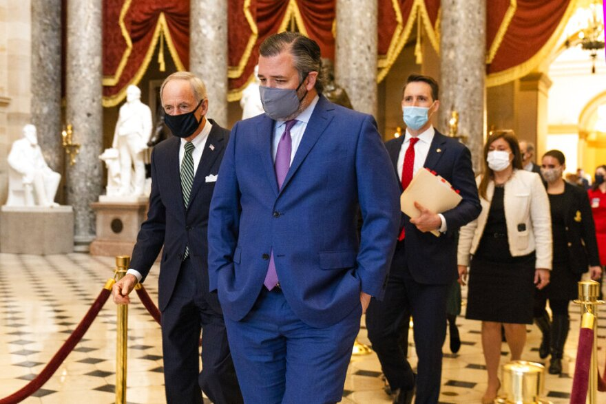 Sen. Ted Cruz, R-Texas, front, followed by Sen. Josh Hawley, R-Mo., walk from the House Chamber following a Senate procession carrying boxes holding Electoral College votes to the House Chamber for a joint session to confirm the Electoral College votes. (Manuel Balce Ceneta/AP Photo)