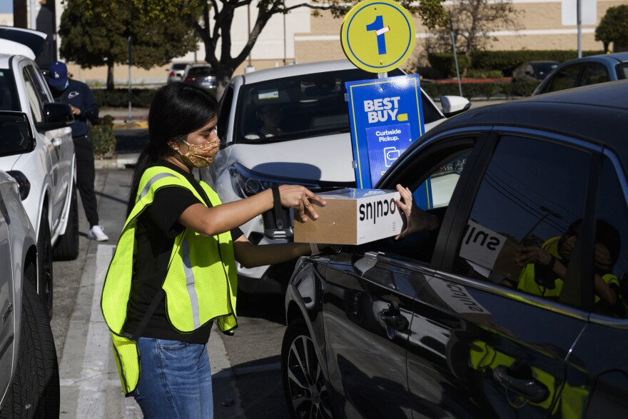A Best Buy employee delivers a curbside pickup order to a customer's vehicle on Friday in Hawthorne, Calif.