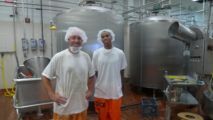 """Inside the secure perimeter in the milk processing facility at Corcoran state prison, Ryan Mons (left) and Edward Wilson give a tour. Wilson's job involves testing the milk for bacteria. """"I take pride in what I do,"""" he says."""
