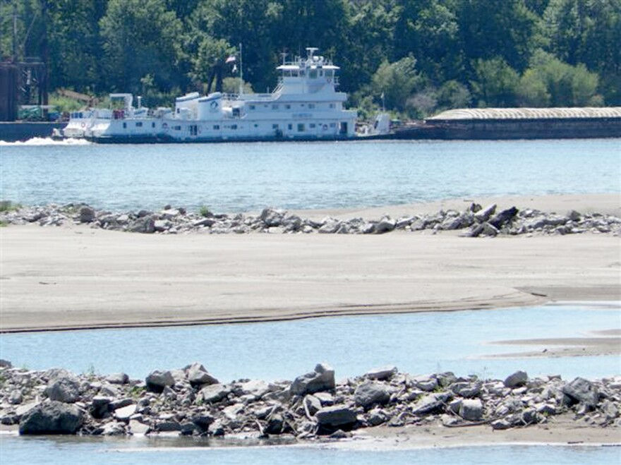 A tow pushes a barge past a sandbar on the Mississippi River near the confluence with the Missouri River north of St. Louis., on Friday. Many sandbars normally under water on the two rivers are now exposed as the drought has caused river levels to drop.