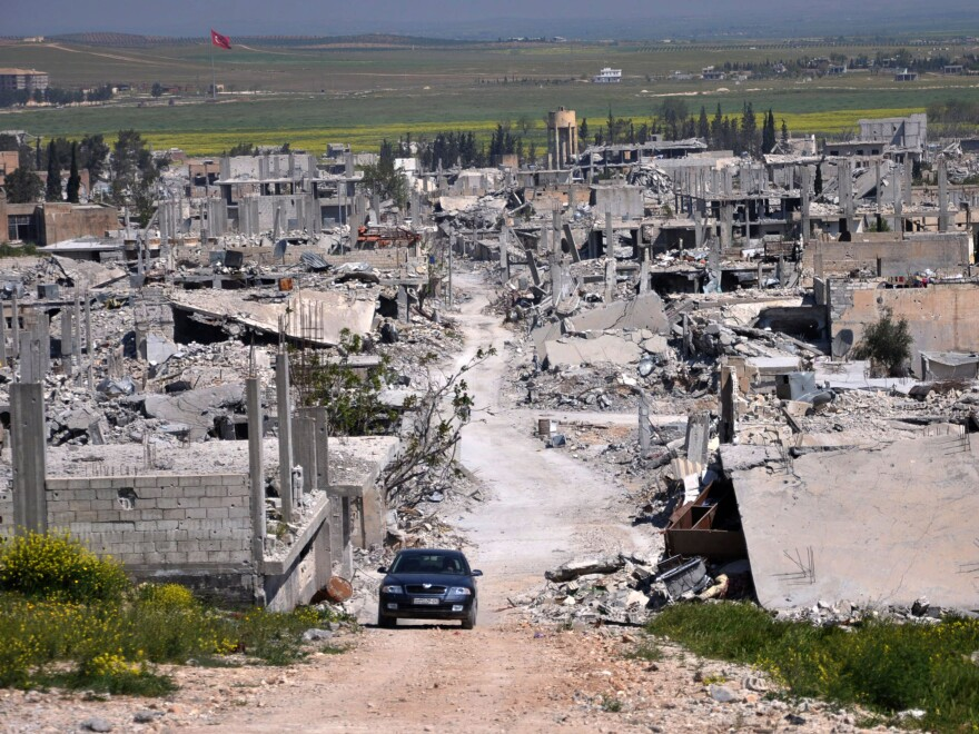 A car passes in an area that was destroyed during the battle between the U.S. backed Kurdish forces and the Islamic State fighters in Kobani, north Syria, in 2015.